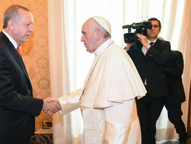 Presiden Turki Recep Tayyip Erdogan (kiri) bersalaman dengan Paus Fransiskus saat kunjungannya ke Vatikan (5/2). Erdogan menjadi Presiden Turki pertama selama 59 tahun yang mengunjungi Paus Fransiskus di Vatikan. (Alessandro Di Meo / Pool via AP)