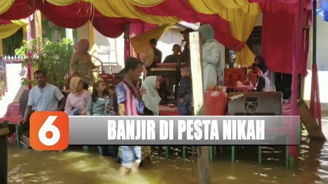Pasangan di Aceh Barat, Aceh, harus menggelar pesta pernikahan di tengah banjir setinggi 30 cm.