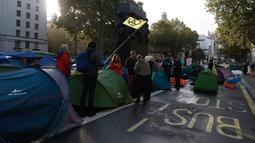 Aktivis iklim mengibarkan bendera ketika mereka berkemah di Whitehall, London, Inggris, Selasa (8/10/2019). Gerakan ini termasuk dalam pemberontakan internasional yang juga berlangsung di beberapa negara, seperti Australia dan Belanda. (AP Photo/Alastair Grant)