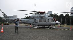 Warga berswafoto dengan helikopter TNI yang terparkir di kawasan Monas, Jakarta, Rabu (16/10/2019). Kehadiran empat helikopter TNI/Polri yang akan digunakan dalam apel pengamanan pelantikan presiden dan wakil presiden tersebut menarik perhatian pengunjung Monas. (merdeka.com/Iqbal Nugroho)