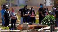 Keluarga Luzia Paulina Santos (82), yang dikatakan meninggal karena COVID-19, menghadiri pemakamannya di pemakaman Campo da Esperanca di Brasilia, Brasil, Kamis (3//9/2020). Brasil melaporkan rata-rata lebih dari 1.000 kematian setiap hari akibat corona sejak akhir Mei. (AP Photo/Eraldo Peres)