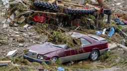 Mobil-mobil hancur terlihat akibat dilanda banjir setelah hujan deras yang turun yang membuat sungai Ahr meluap di Schuld, Jerman, Kamis (15/7/2021). Hujan diprekdiksi akan terus turun dalam beberapa hari ke depan. (AP Photo/Michael Probst)