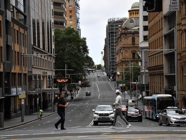 Pejalan kaki melintasi jalan yang biasanya padat dengan lalu lintas di kawasan pusat bisnis di Sydney, Rabu (30/12/2020). Pihak berwenang berupaya menekan klaster kasus virus corona Covid-19 yang terus bertambah di kota terpadat di Australia tersebut. (Saeed KHAN / AFP)