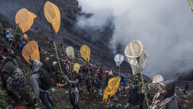 Orang-orang mencoba menangkap sesajen yang dilemparkan suku Tengger ke kawah Gunung Bromo saat upacara Yadnya Kasada di Probolinggo, Jawa Timur, Sabtu (26/6/2021). Suku Tengger mempersembahkan sesajen berupa beras, buah, ternak, dan barang lainnya untuk mencari berkah dari dewa. (Juni Kriswanto/AFP)