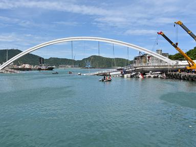Sebuah jembatan  yang ambruk di pelabuhan ikan Nanfangao di kota Suao (1/10/2019). Jembatan beton yang ambruk tersebut menimpa beberapa perahu nelayan yang bersandar di bawahnya. (AFP Photo/Sam Yeh)