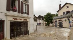 Seorang pria berada di jendela lantai pertama menyaksikan banjir merendam jalanan setelah hujan lebat di Salies-de-Bearn, Perancis barat daya (13/6). (AFP Photo/Iroz Gaizka)