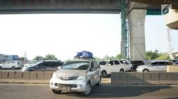 Kendaraan pemudik menerobos pagar pembatas jalan tol di KM 30 Tol Jakarta - Cikampek, kawasan Cikarang, Jawa Barat, Minggu (9/6). Kemacetan yang terjadi di sepanjang jalur tersebut menyebabkan sebagian kendaraan nekat menerobos pagar pembatas untuk berpindah jalur. (Liputan6.com/Immanuel Antonius)