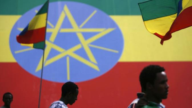 Warga melintas di depan replika raksasa bendera Ethiopia (AFP/Jose Cendon)