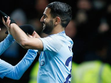 Gelandang Manchester City, Riyad Mahrez (kanan) berselebrasi dengan Bernardo Silva usai mencetak gol ke gawang Watford pada lanjutan Liga Inggris di stadion Vicarage Road (4/12). City menang tipis atas Watford 2-1. (AP Photo/Frank Augstein)
