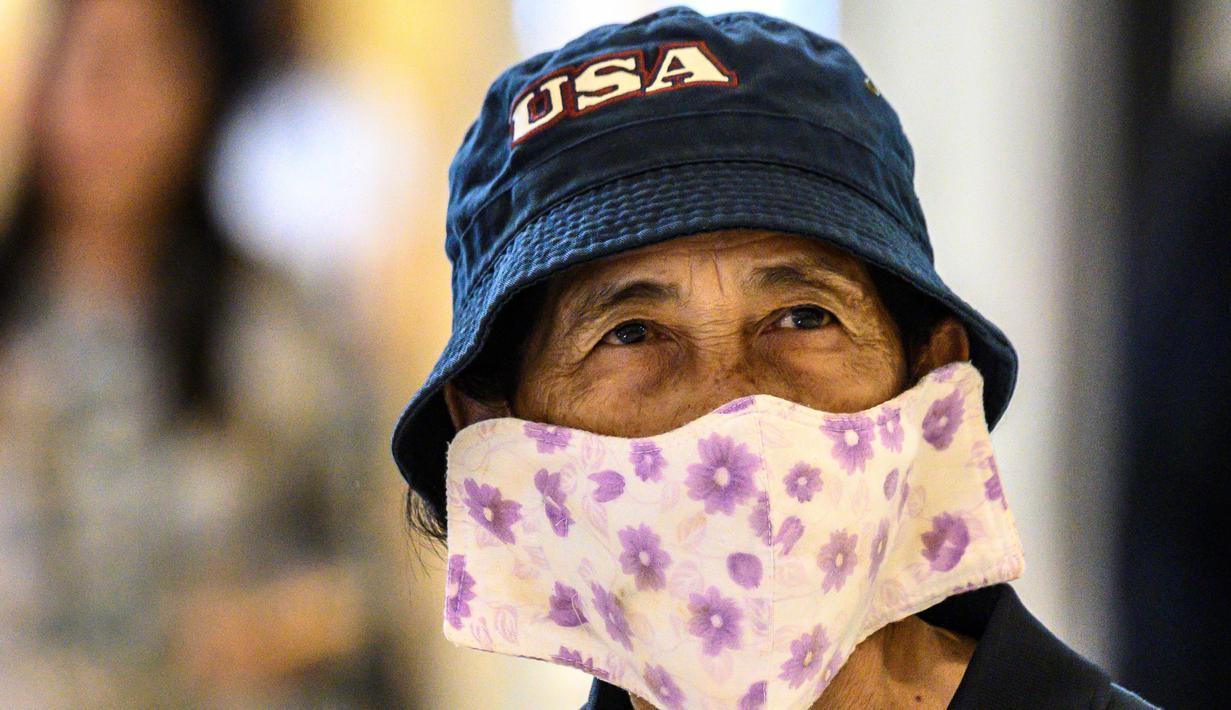 Seorang pengunjung mengenakan masker pelindung di tengah kekhawatiran penyebaran virus corona COVID-19 di sebuah toko di Bangkok, Thailanda (17/2/2020). Penggunaan masker merupakan salah satu cara untuk mengantisipasi penyebaran virus corona. (AFP/Mladen Antonov)