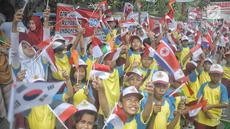 Siswa-siswi SD membawa bendera negara peserta Asian Games 2018 untuk menyambut Kirab Obor di kawasan Jati Padang, Pasar Minggu, Rabu (15/8). Mereka memenuhi jalanan untuk menyaksikan langsung Pawai Obor Asian Games 2018. (Liputan6.com/Faizal Fanani)