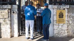 Pengunjung menunggu di depan pintu masuk kedutaan besar Kanada yang berada di Hanava, Kuba, Selasa (17/3).  Kanada memulangkan staf diplomat beserta keluarga mereka dari Kuba karena terserang penyakit misterius. (AP/Desmond Boylan)