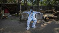 Seorang petugas kesehatan yang kelelahan beristirahat setelah membawa jenazah seseorang untuk dikremasi di Gauhati, India, Selasa (27/4/2021). Kasus virus corona COVID-19 di India melonjak lebih cepat dari tempat lain di dunia. (AP Photo/Anupam Nath)