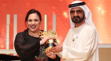 Guru sekolah di tengah wilayah termiskin Inggris, Andria Zafirakou menerima trofi Global Teacher Prize dari Wakil Presiden dan Perdana Menteri UEA, Sheikh Mohammed bin Rashid al-Maktoum dalam acara penganugerahan di Dubai, Minggu (18/3). (AP/Jon Gambrell)