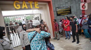 Seorang pengunjuk rasa yang menolak UU Cipta Kerja memeluk orang tuanya di Polda Metro Jaya, Jakarta, Rabu (14/10/2020). Mereka diamankan petugas Kepolisian karena diduga terlibat kericuhan saat unjuk rasa menolak UU Cipta Kerja pada Selasa (14/10/2020). (Liputan6.com/Faizal Fanani)