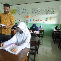 Guru mengajar secara darling sekaligus tatap muka kepada murid-murid SDIT Nurul Amal, Pondok Cabe, Tangerang Selatan, Banten, Senin (16/11/2020).  Proses belajar secara tatap muka atau luring ini merupakan uji coba dengan menggunakan assessment pembatasan jumlah murid. (merdeka.com/Arie Basuki)