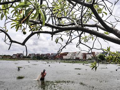 Amir (38) saat menjala ikan di genangan air yang merendam kompleks pemakaman TPU Semper, Jakarta, Selasa (2/2/2021). Banjir yang semakin tinggi merendam TPU Semper hingga mencapai sepinggang orang dewasa. (merdeka.com/Iqbal S. Nugroho)