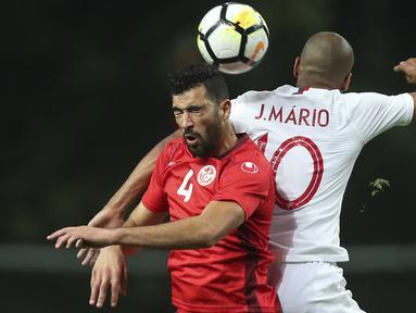 Duel pemain Tunisia, Yassine Meriah (kiei) dan pemain Portugal, Joao Mario pada laga uji coba di Estadio Municipal de Braga, (28/5/2018) waktu setempat. Portugal dan Tunisia bermain imbang 2-2. (AP/Luis Vieira)