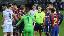 Para pemain Barcelona memprotes keputusan wasit Adrian Cordero Vega (tengah) yang memberikan hadiah penalti kepada SD Huesca dalam laga lanjutan Liga Spanyol 2020/2021 pekan ke-27 di Camp Nou Stadium, Barcelona, Senin (15/3/2021). Barcelona menang 4-1 atas SD Huesca. (AFP/Lluis Gene)
