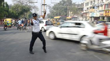 Polisi lalu lintas India Ranjeet Singh mengarahkan lalu lintas di persimpangan Indore, India (22/12). Saat mengatur lalu lintas, Ranjeet Singh menari moonwalk ala Michael Jackson yang menjadi perhatian warga sekitar.  (AFP Photo/Indranil Mukherjee)
