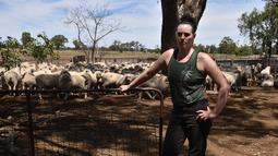 Emma Billet berpose dengan latar belakang kumpulan domba di tempat pemotong bulu domba di New South Wales, Australia (21/2). Dalam sehari Emma dapat mencukur bulu domba sebanyak 120 ekor. (AFP/Peter Parks)