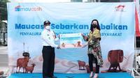 CEO Maucash Rina Apriana (kanan) menyerahkan secara simbolis penyerahan hewan kurban kepada Camat Cilandak Mundari (kiri). Pada hari raya Idul Adha 1442 Hijriyah, Maucash menyalurkan hewan kurban yang akan disalurkan kepada masyarakat sekitar kantor Maucash, Cilandak, Jakarta Selatan.