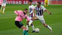Bek Barcelona, Oscar Mingueza, berebut bola dengan bek Valladolid, Nacho Martinez, pada laga lanjutan Liga Spanyol di Jose Zorrilla Stadium, Rabu (23/12/2020) dini hari WIB. Barcelona menang 3-0 atas Valladolid. (AFP/Cesar Manso)