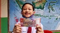 Muhammad Izzam Athaya memamerkan uang kertas pecahan baru yang berisi foto dirinya mengenakan pakaian adat Suku Tidung. (Foto: Siti Hardiani)