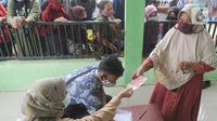 Warga menerima uang Bantuan Sosial Tunai (BST) bulan Januari di halaman Masjid Jami Al-Hidayah RW 01 Bedahan, Depok, Selasa (16/2/2021). Sekitar 159.470 Keluarga Penerima Manfaat (KPM) di Kota Depok menerima BST yang disalurkan PT Pos Indonesia pada Februari ini. (merdeka.com/Arie Basuki)