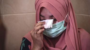 Berda Asmara menghapus air mata saat berbicara tentang suaminya Serda Mes Guntur Ari Prasetyo di rumah mereka di Surabaya, Jumat (23/4/2021). Serda Mes Guntur Ari Prasetya merupakan juru diesel di kapal selam KRI Nanggala-402 yang hilang kontak. (Juni Kriswanto/AFP)