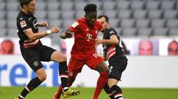 Pemain Bayern Munchen, Alphonso Davies, berusaha melewati pemain Fortuna Duesseldorf pada laga Bundesliga di Allianz Arena, Sabtu (30/5/2020). Bayern Munchen menang 5-0 atas Fortuna Duesseldorf. (AP/Christof Stache)