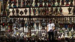 """Pedagang menjual lentera tradisional yang dikenal dalam bahasa Arab sebagai """"Fanous"""" menjelang bulan suci Ramadan di ibu kota Kairo, 19 April 2020. Bagi warga Mesir membeli lentera sudah menjadi tradisi sejak berabad-abad walaupun kini virus corona tengah melanda dunia. (Mohamed el-Shahed/AFP)"""