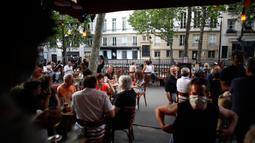 Orang-orang duduk di teras kafe di Paris pada Selasa (2/6/2020). Balai Kota Paris mengizinkan pembukaan area tempat duduk area luar (outdoor) kafe, tetapi di dalam ruangan akan tetap tertutup bagi pelanggan sampai setidaknya 22 Juni mendatang. (AP Photo/Thibault Camus)