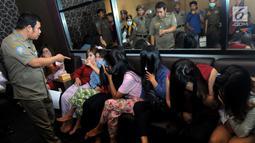 Petugas Satpol PP mengintrogasi sejumlah wanita selama razia panti pijat di BSD, Tangerang Selatan, Selasa (25/6/2019). Dalam razia tersebut puluhan wanita diamankan karena tidak bisa menunjukan kartu identitas. (merdeka.com/Arie Basuki)