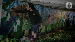 Mahasiswa Institut Kesenian Jakarta (IKJ) menyelesaikan pembuatan mural di kolong Jembatan Pegangsaan, Menteng, Jakarta, Selasa (26/1/2021). Pembuatan mural tersebut bertujuan mempercantik kawasan bantaran kali dan sebagai ruang interaksi warga. (Liputan6.com/Faizal Fanani)