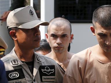 Dua tersangka pemboman Yusufu Mieraili dan Bilal Mohammed berjalan saat tiba di Pengadilan militer (20/4). Yusufu dan Bilal didakwa terkait pemboman sebuah kuil di Bangkok yang terjadi pada 17 Agustus 2015 lalu. (REUTERS/Chaiwat Subprasom)