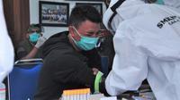 Pemain Arema FC, Dedik Setiawan, meringis menahan sakit ketika darahnya akan diambil untuk rapid test, Jumat (17/7/2020). (Bola.com/Iwan Setiawan)