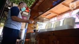 Megah Putra Perkasa, pilot komersial maskapai nasional di Tanah Air, meracik mie ayam di kiosnya Kawasan BSD City, Tangerang Selatan, Rabu (12/8/2020). Masa pandemi yang membuat jasa penerbangan harus terhenti ini membuat Megah Putra banting setir menjadi penjual mie ayam. (merdeka.com/Dwi Narwoko)