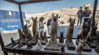 Patung-patung kucing ditampilkan setelah serangkaian penemuan langka di Saqqara, selatan Kairo, Sabtu (23/11/2019). Mumi hewan seperti anak singa, kucing, kobra, buaya, hingga kumbang ditemukan oleh tim arkeologi Mesir, termasuk 75 patung kayu dan perunggu dari masa silam. (Khaled DESOUKI/AFP)