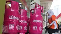 Petugas Bright Store menata tabung - tabung gas elpiji berwarna pink ukuran 5,5kg di SPBU Pertamina Abdul Muis, Jakarta,Senin (19/10/2015).