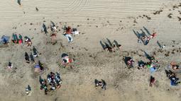 Pemandangan udara dari orang-orang di pantai di Playas de Tijuana dekat perbatasan AS-Meksiko di Tijuana, negara bagian Baja California, Meksiko, Sabtu (3/10/2020). Akhir pekan ini pantai di Playas de Tijuana dibuka kembali setelah ditutup sejak Maret lalu akibat Covid-19. (Guillermo Arias/AFP)