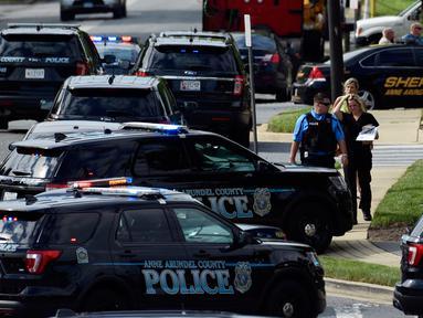 Aparat kepolisian mengamankan lokasi penembakan brutal di kantor surat kabar lokal Capital Gazette di Annapolis, Amerika Serikat (AS), Kamis (28/6). Akibat penembakan ini lima orang tewas dan tiga lainnya luka parah. (AP/Susan Walsh)