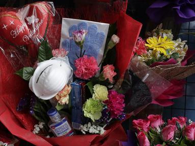 Paket rangkaian bunga Valentine di Alabang, Manila, Filipina (13/2/2020). Pemilik toko Mary Jane Villegas sengaja meletakkan keperluan perlindungan terhadap COVID-19 di karangan bunga untuk mengingatkan, bunga bukan satu-satunya yang dapat diberikan saat Valentine. (AP Photo/Aaron Favila)