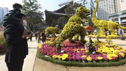 Seorang anak laki-laki dan ayahnya melihat Jam tangan dinosaurus yang terbuat dari bunga krisan selama festival Krisan di kuil Chogyesa di Seoul, Senin (19/10/2020). Korsel mulai menguji puluhan ribu karyawan rumah sakit dan panti jompo untuk mencegah wabah COVID-19. (AP Photo/Ahn Young-joon)