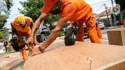 Petugas PPSU memproduksi peti jenazah di halaman Kantor Kelurahan Kayu Putih, Jakarta, Selasa, (6/7/2021). Kelurahan Kayu Putih berinisiatif membuat peti jenazah dilatar belakangi warganya yang terkendala ketersediaan peti saat angka kematian COVID-19 meningkat di DKI. (Liputan6.com/Faizal Fanani)