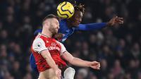 Striker Chelsea, Tammy Abraham, berebut bola dengan bek Arsenal, Shkodran Mustafi, pada laga Premier League pekan ke-24 di Stamford Bridge, London, Rabu (22/1). Arsenal tahan imbang Chelsea 2-2. (AFP/Daniel Leal-Olivas)