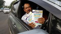 Pengendara mobil menunjukkan selebaran sosialisasi pemberlakuan sistem ganjil genap di pintu masuk Gardu Tol Cibubur 2, Jakarta, Senin (16/4). Kebijakan ini diterapkan untuk mengurai kemacetan di ruas Tol Jagorawi. (Liputan6.com/Faizal Fanani)