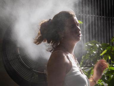 Seorang perempuan mendinginkan tubuh di depan kipas yang menyemprotkan uap air selama gelombang panas di Madrid, Spanyol, Sabtu (14/8/2021). Spanyol mengalami hari terpanas sepanjang tahun pada hari Sabtu dengan suhu mencapai 46 derajat Celcius. (AP Photo/Andrea Comas)