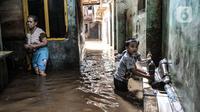 Anak-anak bermain air saat banjir merendam permukiman Kebon Pala, Jatinegara, Jakarta, Minggu (25/10/2020). Tidak adanya tanggul antara permukiman dan Kali Ciliwung menyebabkan banjir yang meluap sejak dini hari tadi lambat surut. (merdeka.com/Iqbal Nugroho)
