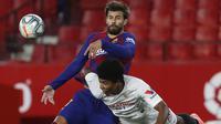 Bek Barcelona, Gerard Pique, berebut bola dengan pemain Sevilla, Jules Kounde, dalam laga lanjutan La Liga Spanyol, Sabtu (20/6/2020) dini hari WIB. Barcelona bermain imbang 0-0 atas Sevilla. (AP/Angel Fernandez)